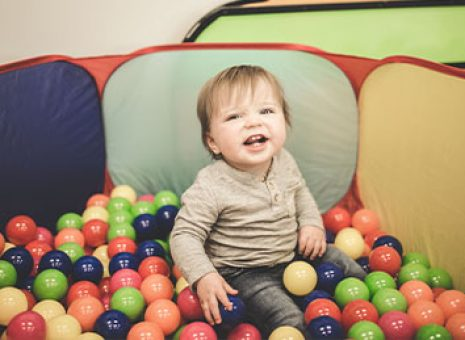 toddler smiling in childcare room surrounded by toys